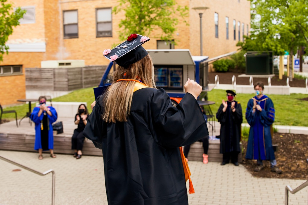 A 2021 graduate is being cheered on my faculty and staff members upon exiting t…