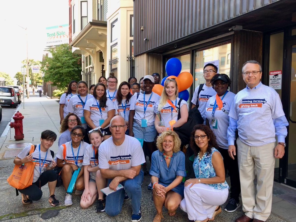 Student volunteers pose on the sidewalk in front of one of the First Year Day o…
