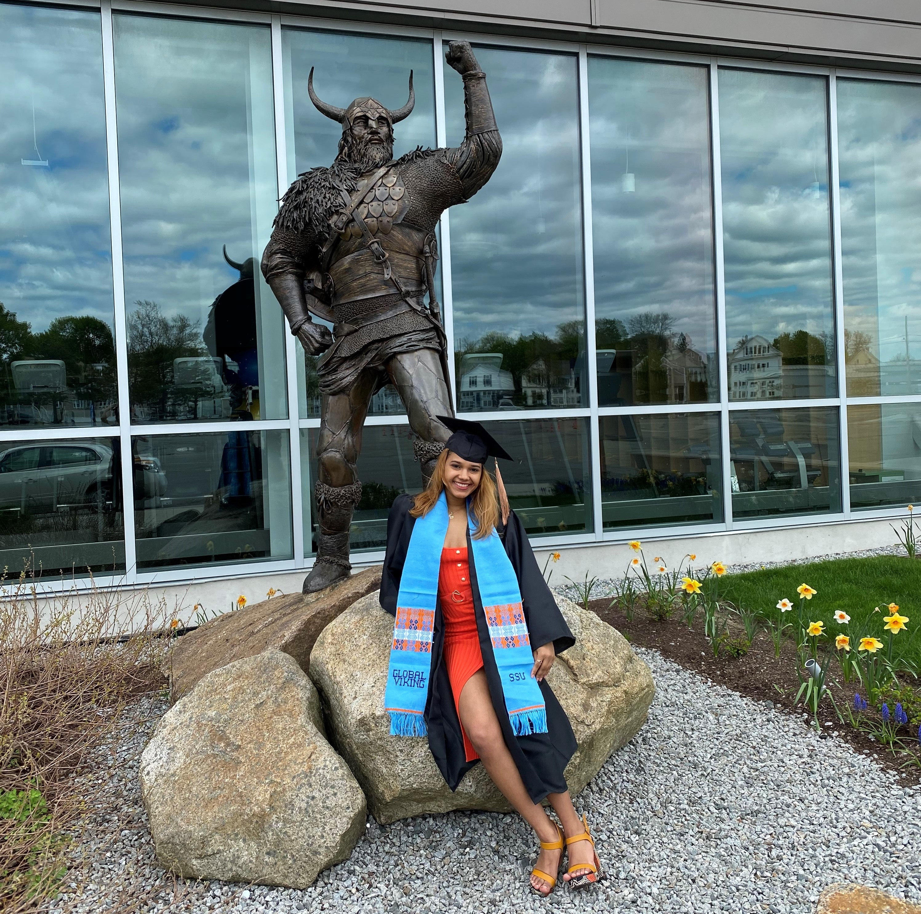 Lishberny Alcantara '20 in graduation cap and gown in front of the Gassett Fitn…
