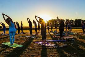 People participating in a yoga class outdoors at sunset