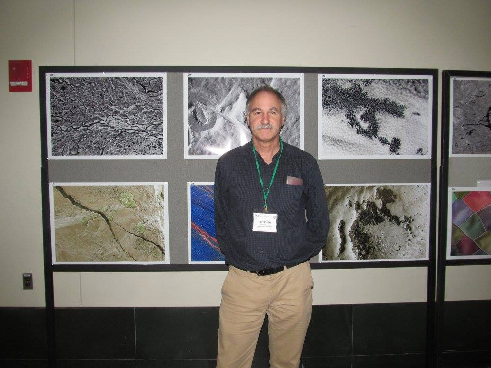 """Professor Young with his exhibit """"Macro or Micro?"""" at the AAG 2017"""