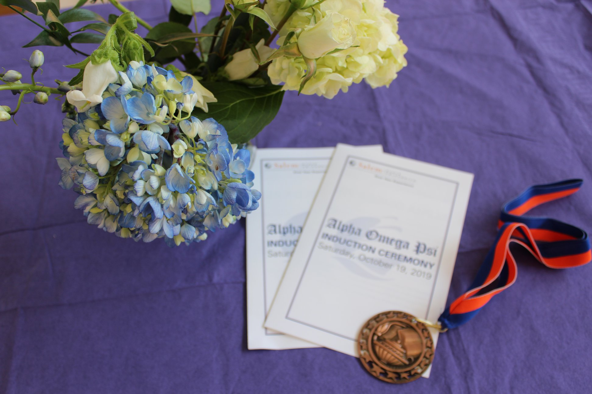 Image of flowers, induction brochure, and medallion for Alpha Omega Psi