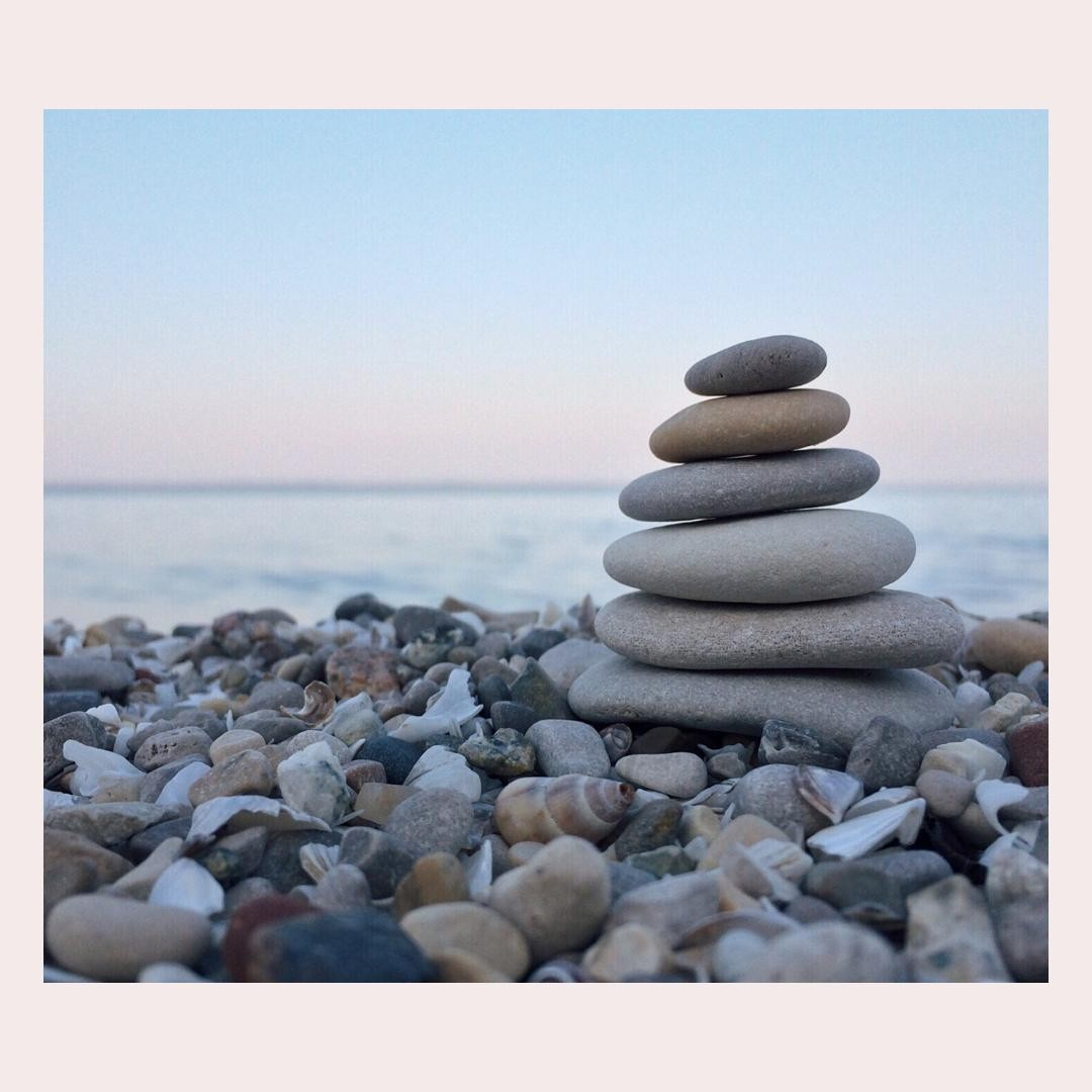 An image of 6 rocks stacked on top of one another over many other rocks and she…