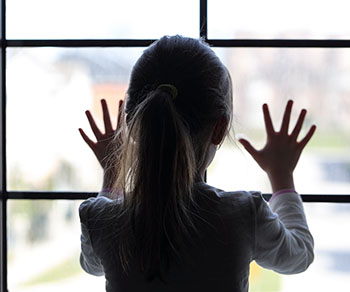 A young female child presses her hands against a window in this photograph