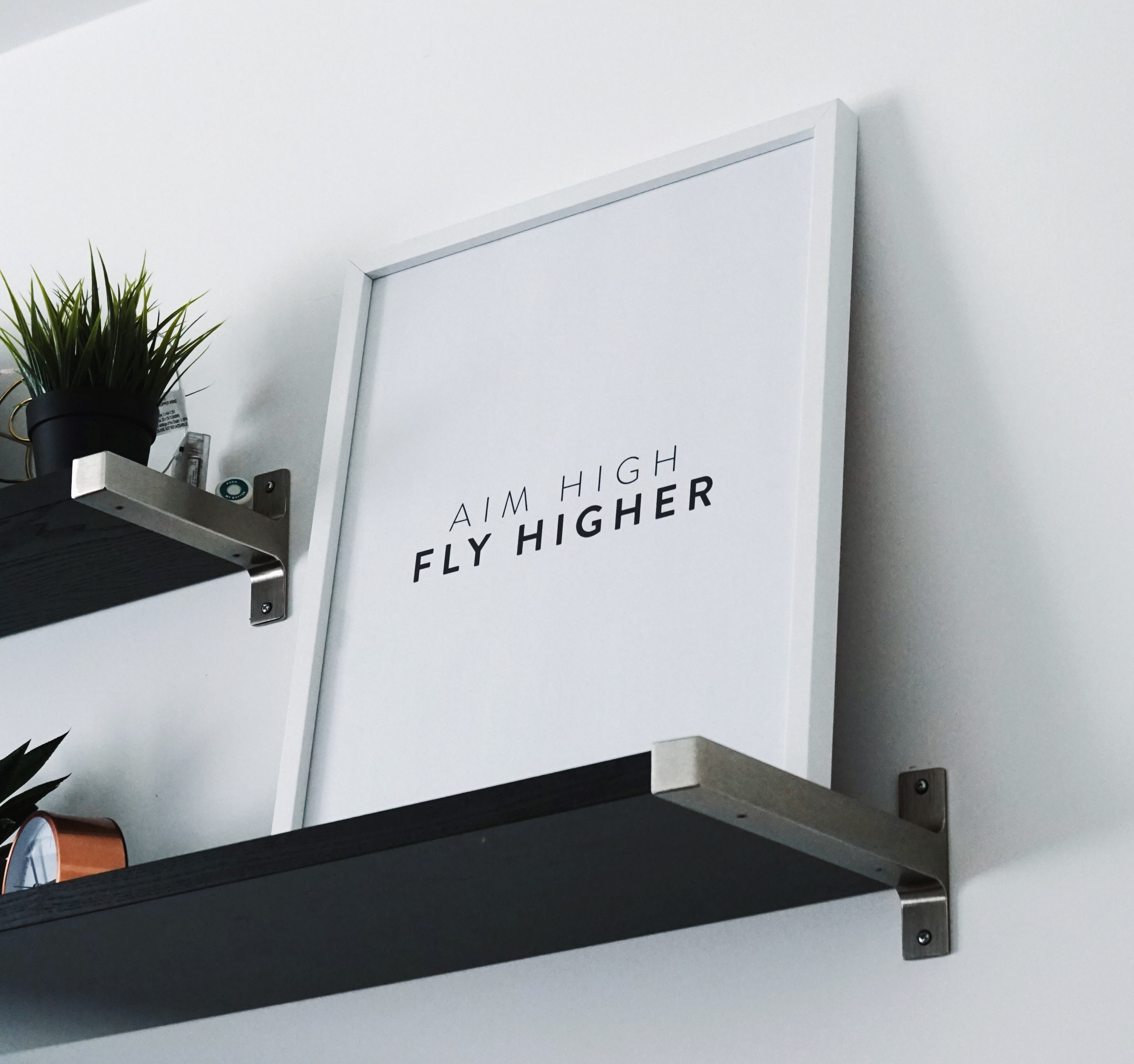 Picture of a framed quote - Aim High, Fly Higher.