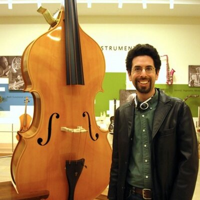 Erik Bauer stands next to a string instrument. Bauer, a Salem State history alu…