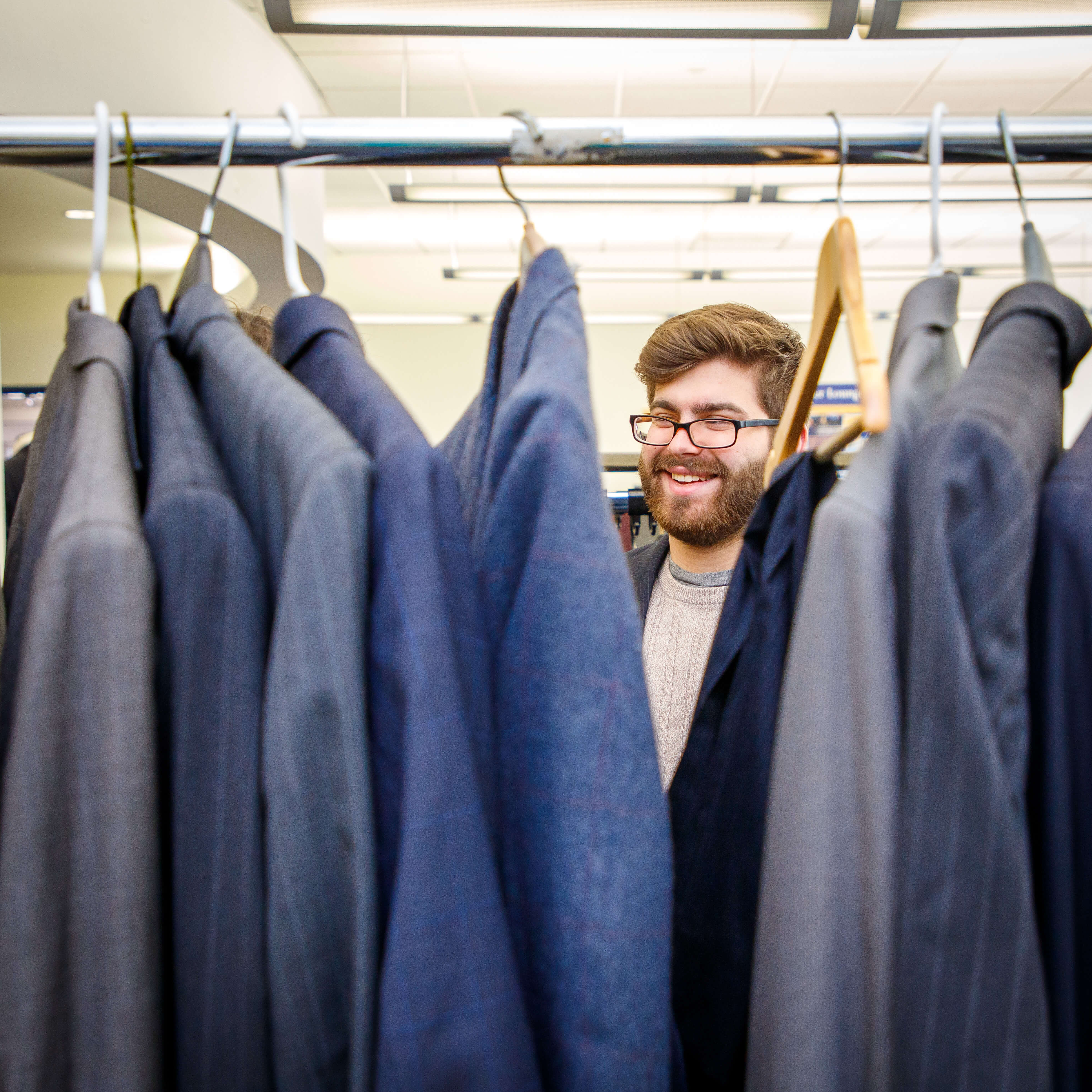 A student looks through professional suit coats at the Career Closet event at S…