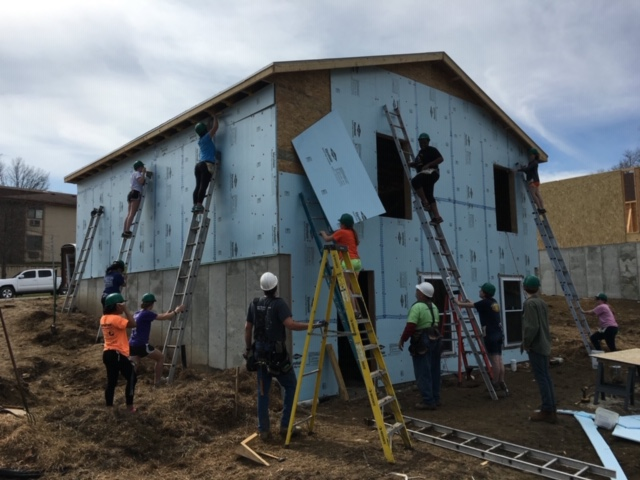 Student volunteers building a house