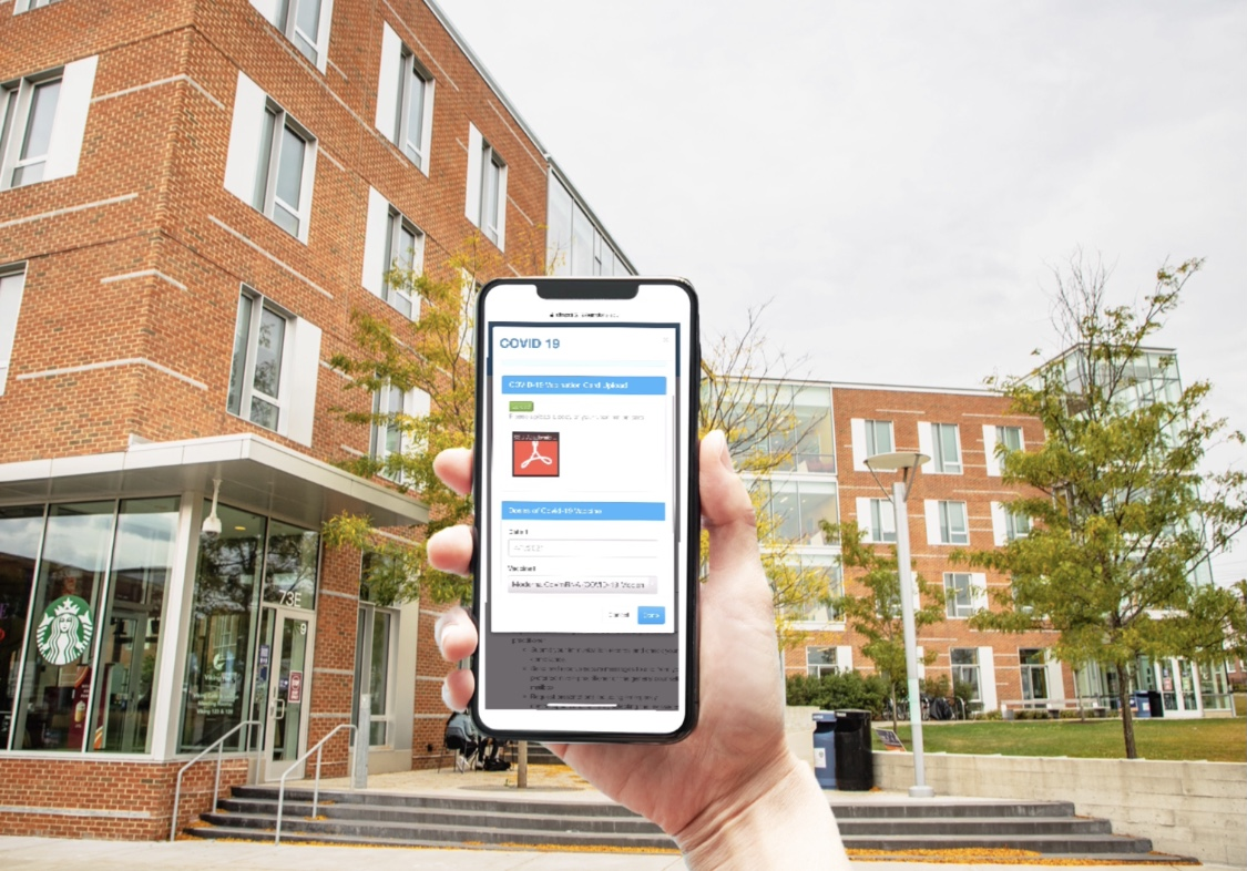 A hand holds up a cellphone screen showing the Salem State vaccine card submiss…