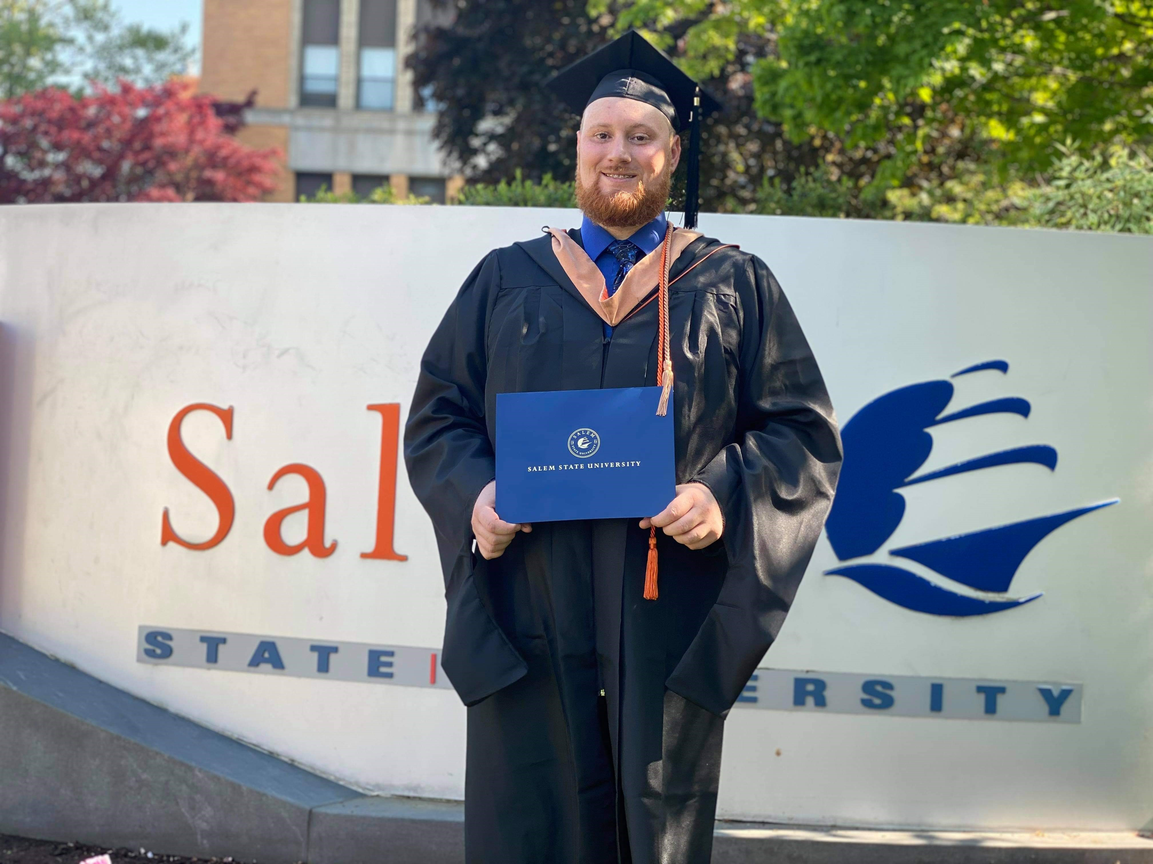 Brian D'Amico, in cap and gown, holds his diploma holder in front of the Salem …