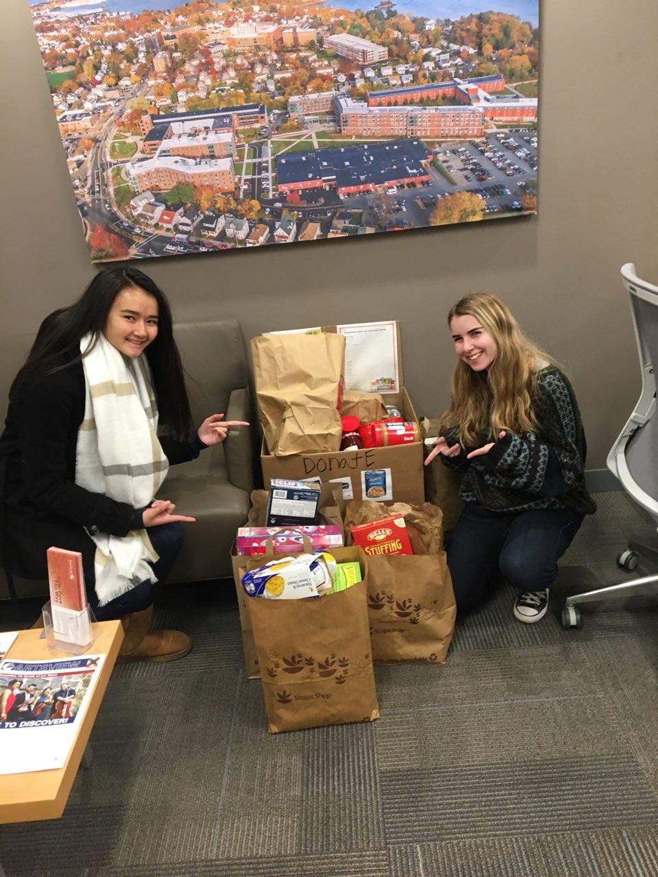 Students from Community Service Initiative point to food collected at a food dr…