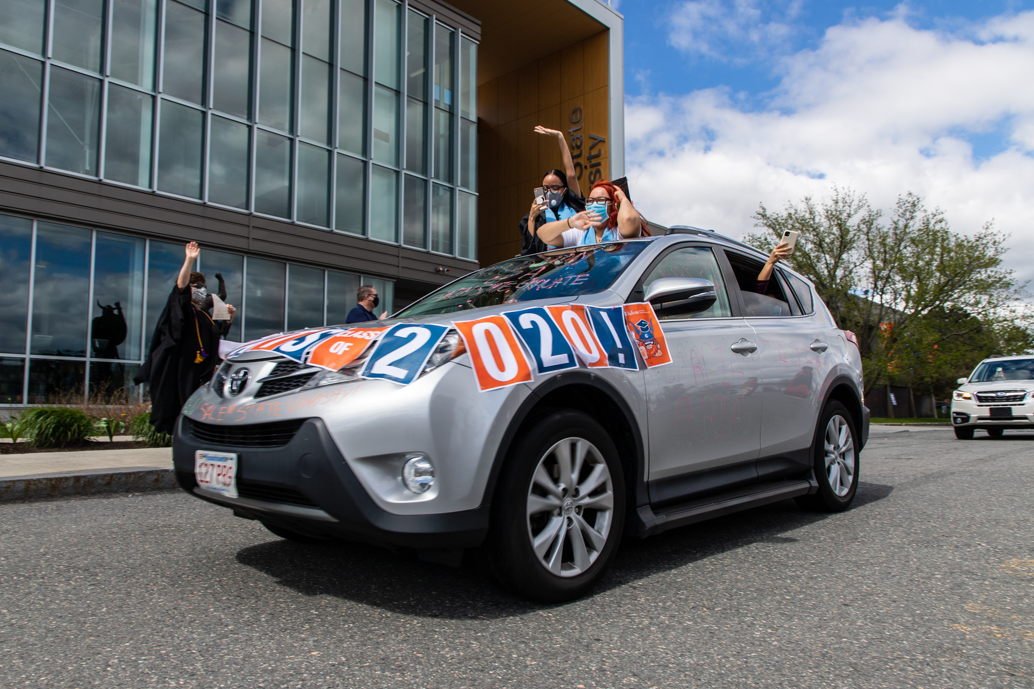 Graduates wave from the sunroof of a car during the Class of 2020 Salem State d…