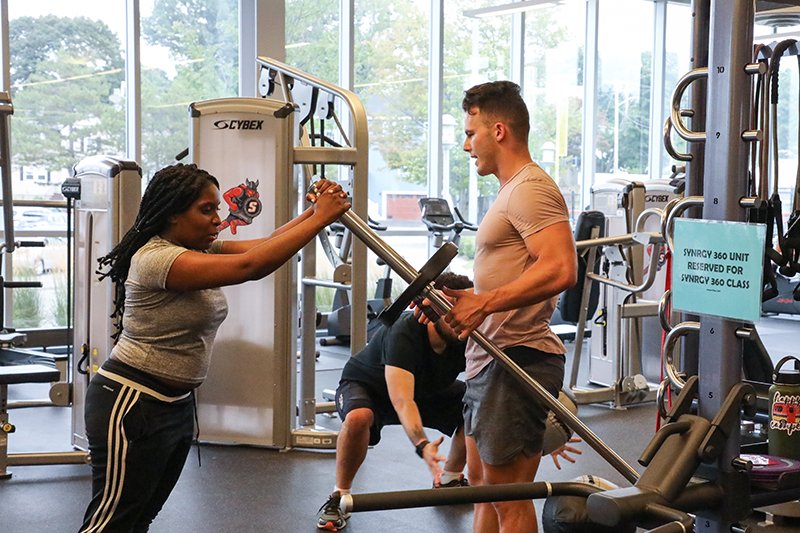 Two students working out on the SYNRGY machine in the fitness center